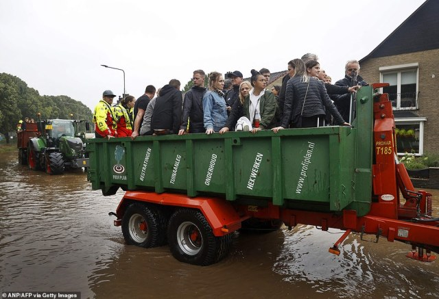 People ride on a trailer as the Dutch fire brigade evacuate people from their homes in South Limburg