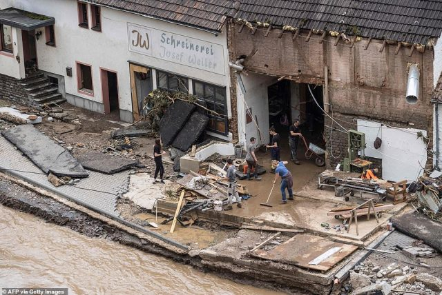 People try to remove the floods from a destroyed house in Schuld near Bad Neuenahr, western Germany