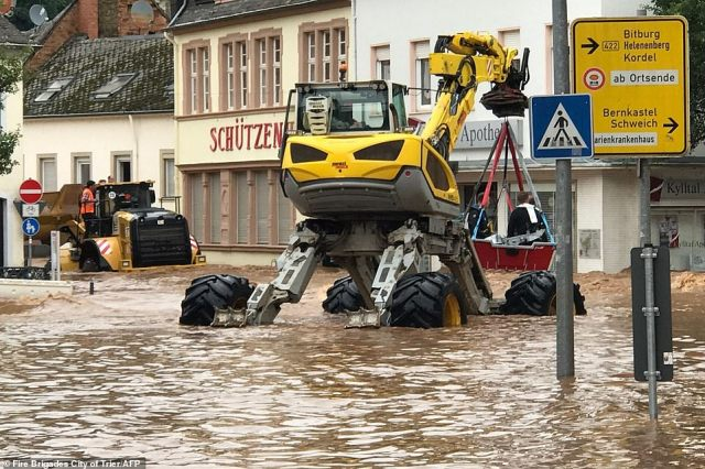 A rescue boat is carried by a special purpose vehicle in the flooded Ehrang neighbourhood in Trier, western Germany