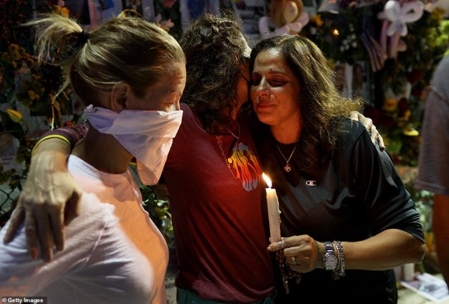 Michelle D'Antuono, Dana Kulvin, and Soraya Batista hug as they visit the memorial that has pictures of some of the victims