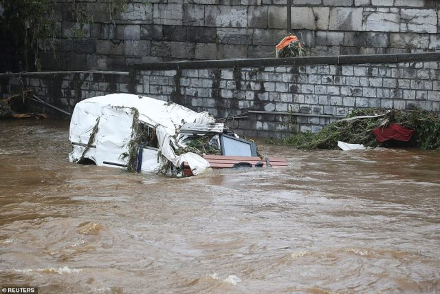 A vehicle and wreckage lie on the river, following heavy rainfalls in Verviers, Belgium, where at least 11 people have died