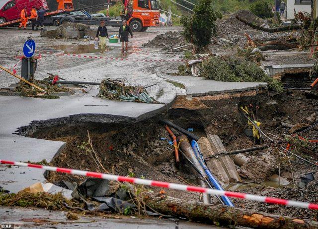 People carry their belongings past a broken road in Schuld, Germany