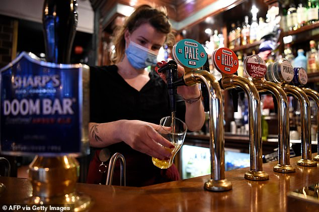 UKHospitality estimates one in five hospitality staff are currently having to self-isolate after being pinged by the Covid app. Pictured: A worker wears a mask at a pub in London's Mayfair
