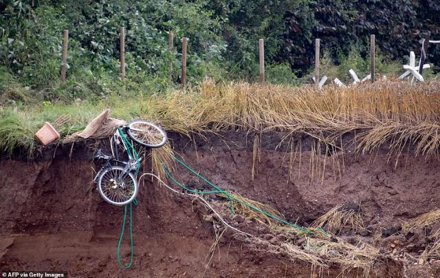 A bicycle that was tied up outside a house in Blessem now hangs on the edge of a giant hole after the ground fell away