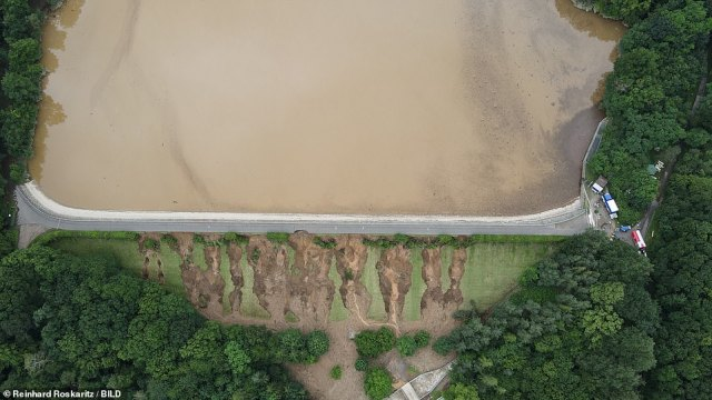 Engineers warned a huge amount of pressure has built up behind the dam after it was inundated with water and its drainage system jammed, with huge cracks visible in the soil wall helping to hold it up (pictured bottom)