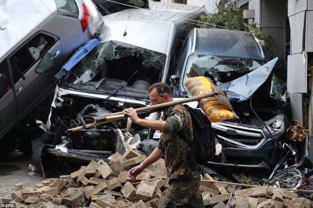 A man carrying a shovel on his shoulder walks amid the debris near damaged cars after flooding in Bad Neuenahr-Ahrweiler