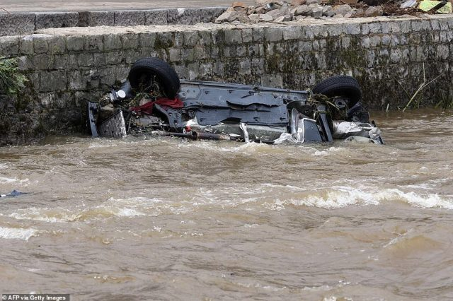 A damaged car lying in a river after the floods caused major damage in Theux, near Liege, Belgium