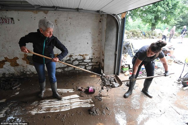 Women remove the mud and debris from the garage following rain storms which flooded the town of Rochefort, Belgium
