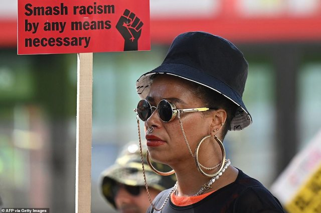 A protester holds a placard as she takes part in a demonstration organised by the Stand Up To Racism group in London today