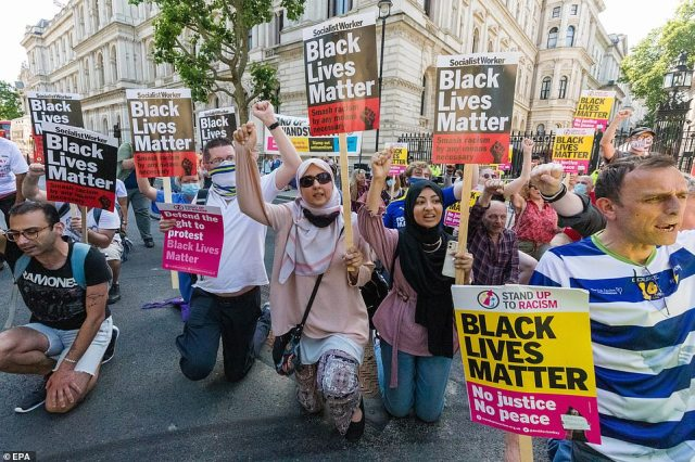 Demonstrators from Stand Up To Racism stage an anti-racism protest against Downing Street in London this afternoon
