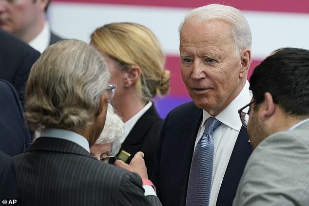 President Joe Biden talks with the Rev. Al Sharpton after his speech