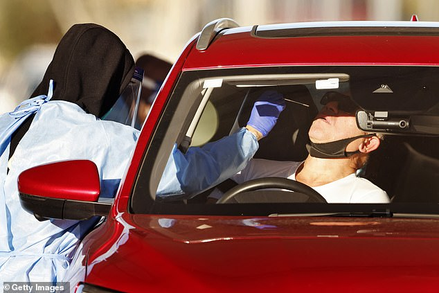 A medical worker tests a driver on Sunday at a 24-hour Covid-19 test clinic in Fairfield West, with the city's southwest becoming the epicenter of the outbreak