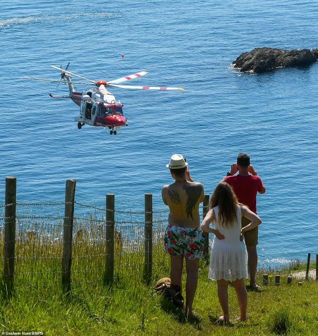 A coastguard helicopter lands on the beach at Durdle Door in Dorset to deal with a medical emergency