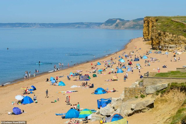 Meanwhile in Hive Beach at Burton Bradstock in Dorset, crowds of visitors begin to flock to the region to bask in the sun