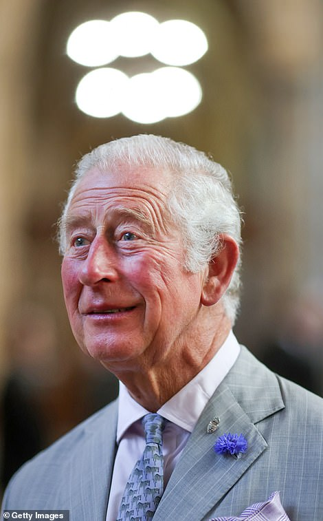Lightbulb moment? Prince Charles, wearing his trusty thistle beside a silver pin, is seen stood beneath a circular light fitting at Exeter Cathedral