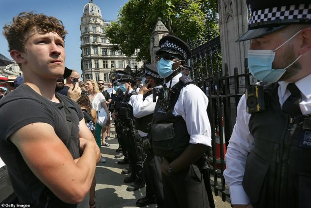 Protesters confront a police line at the Houses of Parliament during today's demonstration