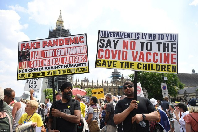 Anti-vaccination protesters hold a demonstration in Parliament Square today as they hold up placards
