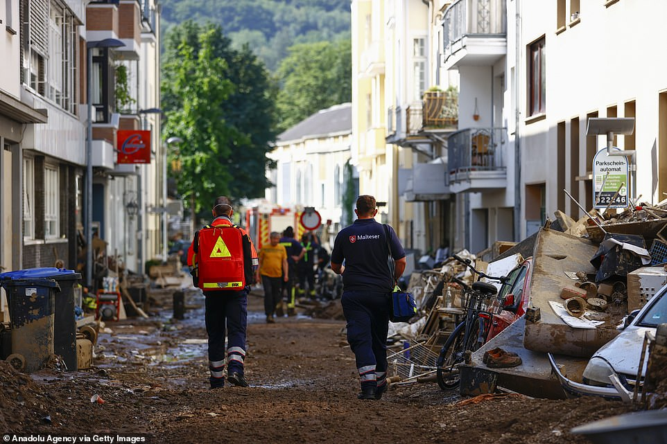 Emergency workers walk down a partially-cleared street inBad Neuenahr, Germany, amid cleanup from the flooding