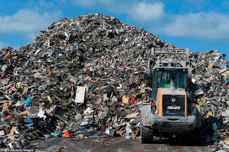 A digger piles rubbish collected from the flooded areas, at a landfill in Rochefort, Belgium
