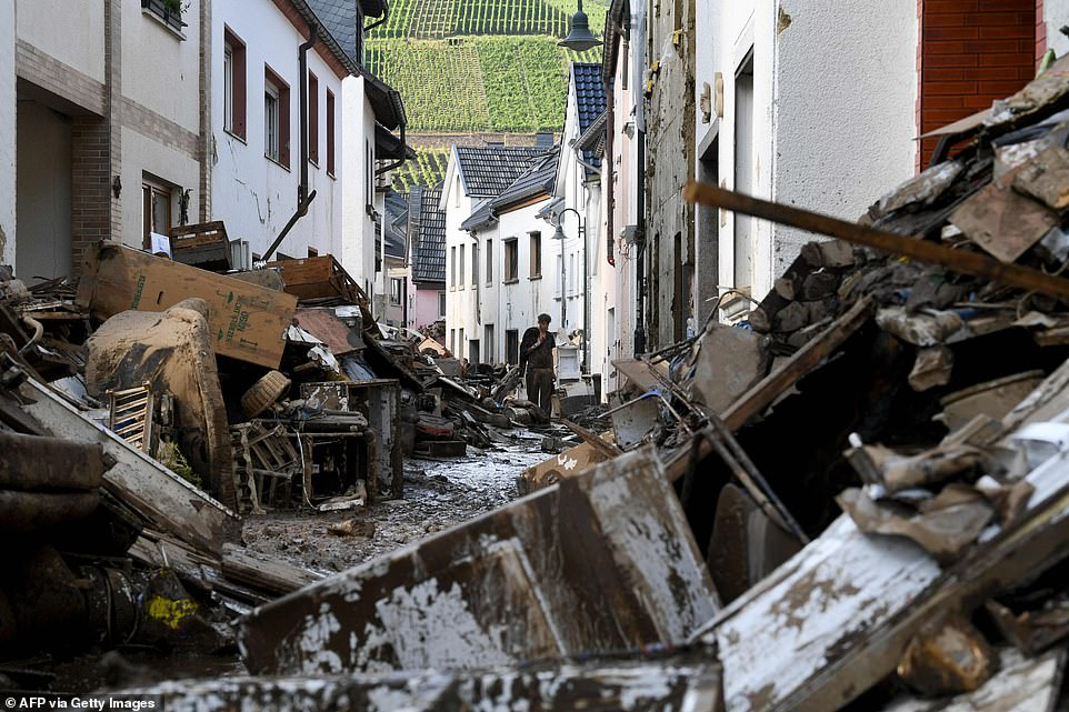 A resident walks in a muddy street full of debris and destroyed furniture and household goods in the city of Dernau
