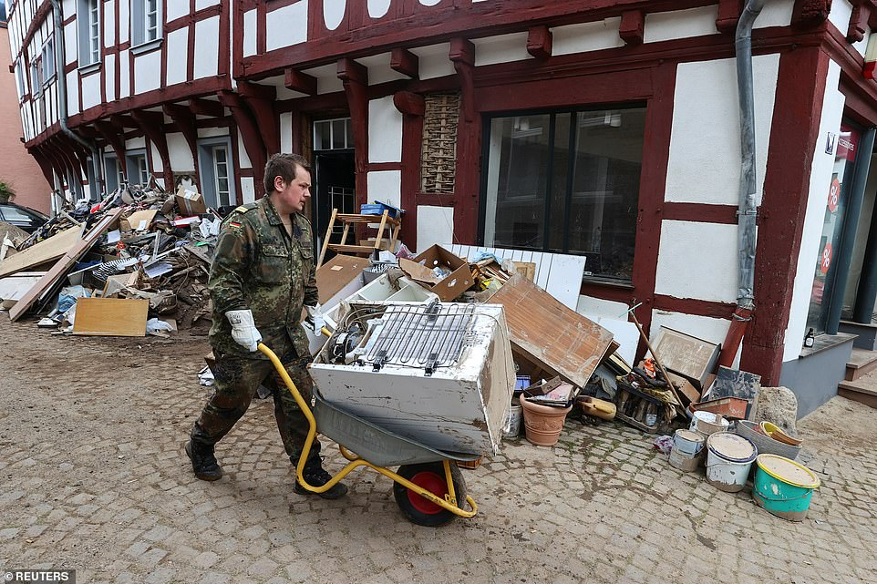 A member of the German armed forces helps carry away a fridge destroyed during flooding inBad Muenstereifel