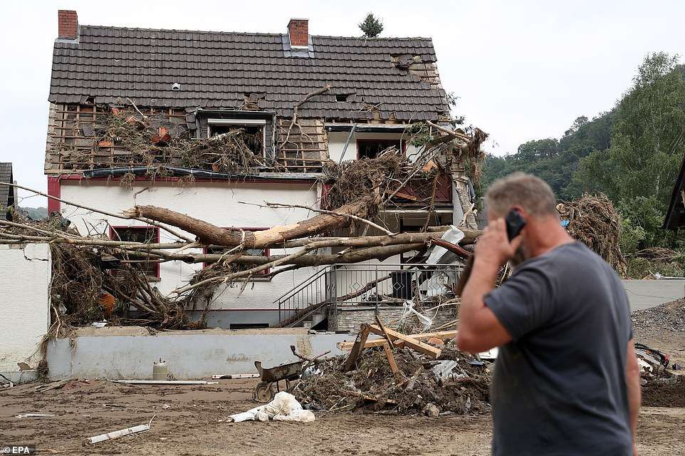 A man walks past a house in Altenahr, Germany, after it was destroyed in severe flash floods following days of continuous rain