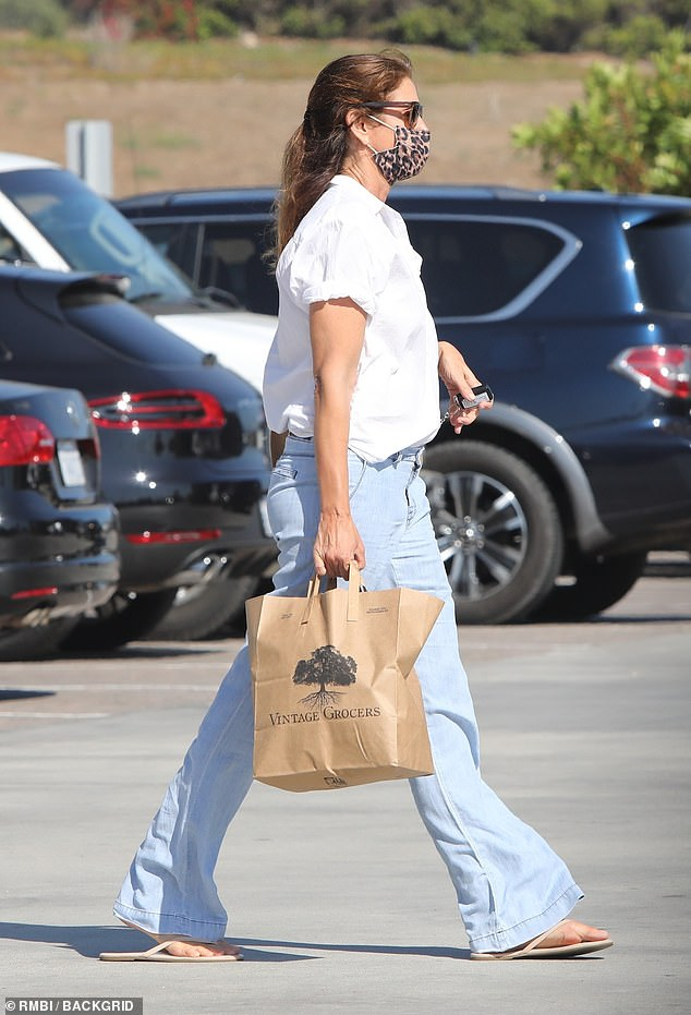 Shopping trip: She carried a leather purse over one shoulder and a store paper bag filled with her purchases