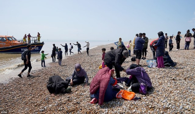 People thought to be migrants make their way up the beach after arriving on a small boat at Dungeness in Kent