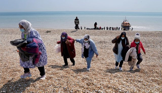 Some raised their hands in celebration as they stood on the beach, while others sat down on the shingle shoreline amid 75.2F (24C) sunshine