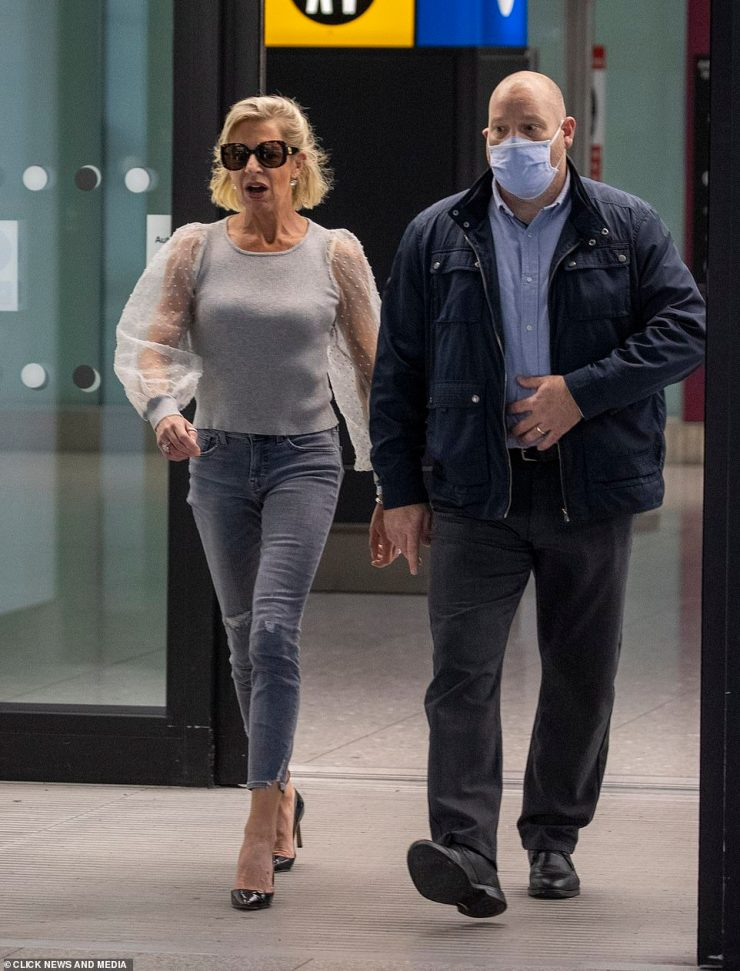 Katie Hopkins has been pictured landing at London Heathrow Airport this morning following her deportation from Australia after she mocked the country's hotel quarantine rules and calling Covid lockdowns the 'greatest hoax in human history'