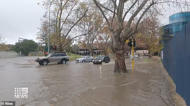 Perth residents are seen trying to make it through floodwaters earlier this month