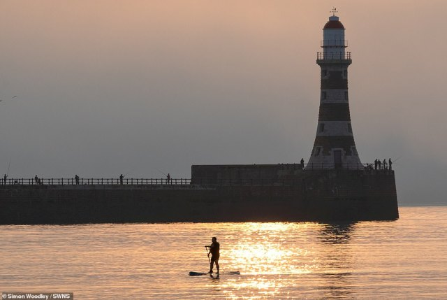 The hot sun burns off the sea mist at sunrise as a paddleboarder goes across Roker Harbour to Roker Lighthouse in Sunderland this morning
