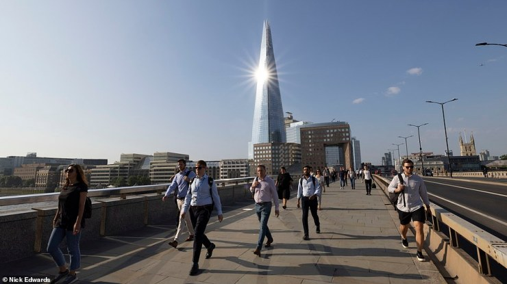 Commuters cross London Bridge in the sun this morning as scorching temperatures continue to hit Britain this week