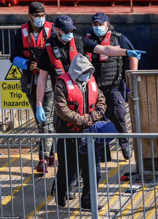 A migrant is escorted by Border Force officers as he is brought ashore at Dover Harbour in Kent after crossing the Channel