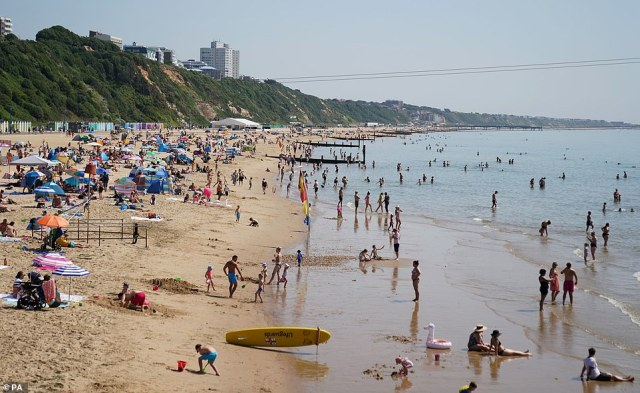 Hundreds of people have taken to beaches across the UK today, as the summer sun looks set to continue. Pictured: People pack out Bournemouth Beach, Dorset on Tuesday, July 20