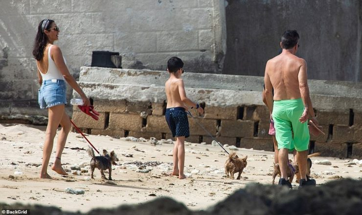 Family break: Simon was seen heading out to walk their dogs on the beach with Lauren and their son Eric, seven