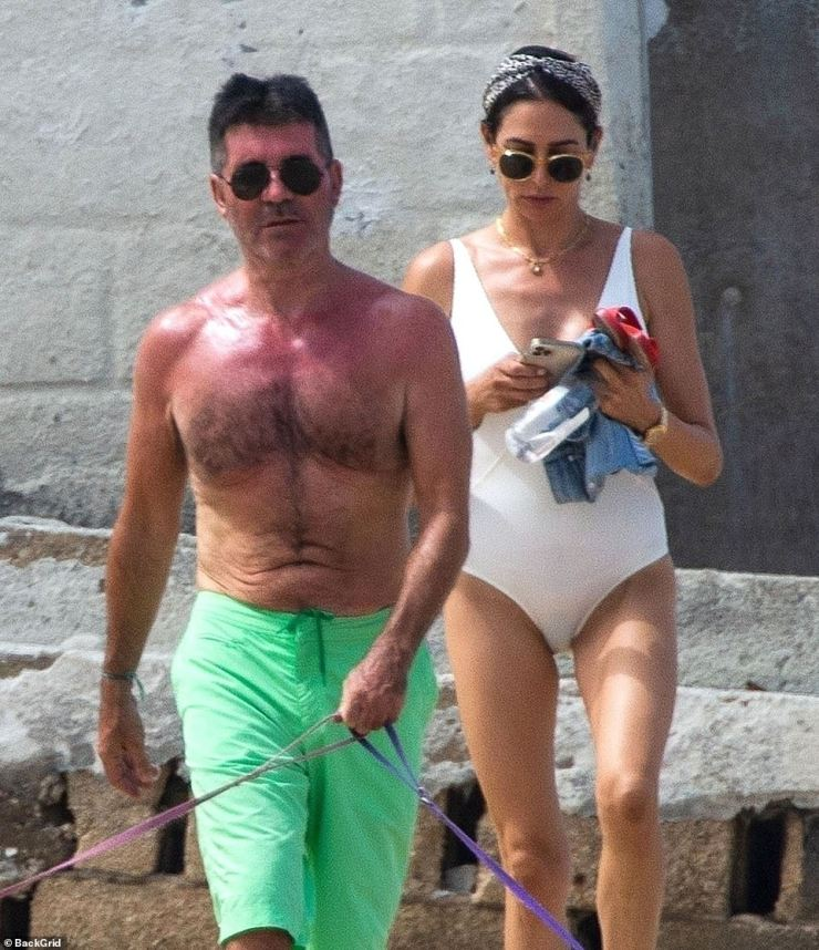 Family break:Simon Cowell's girlfriend Lauren Silverman slipped into a plunging white swimsuit on Monday as she joined the music mogul on the beach in Barbados