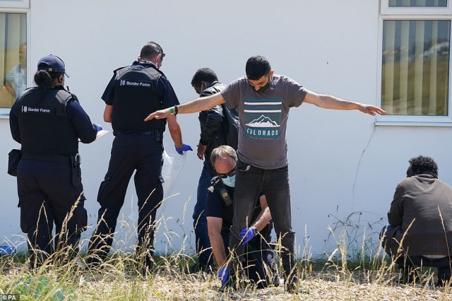 A man thought to be migrant, is search by a Border Force officer after being escorted from the beach in Dungeness, Kent
