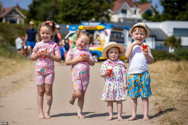 Twins Bella and Layla Hughes (4) with Annie Shepherd (2) and her brother Jude Shepherd (5) eating screwball ice creams at Helen's Bay beach in County Down, Northern Ireland