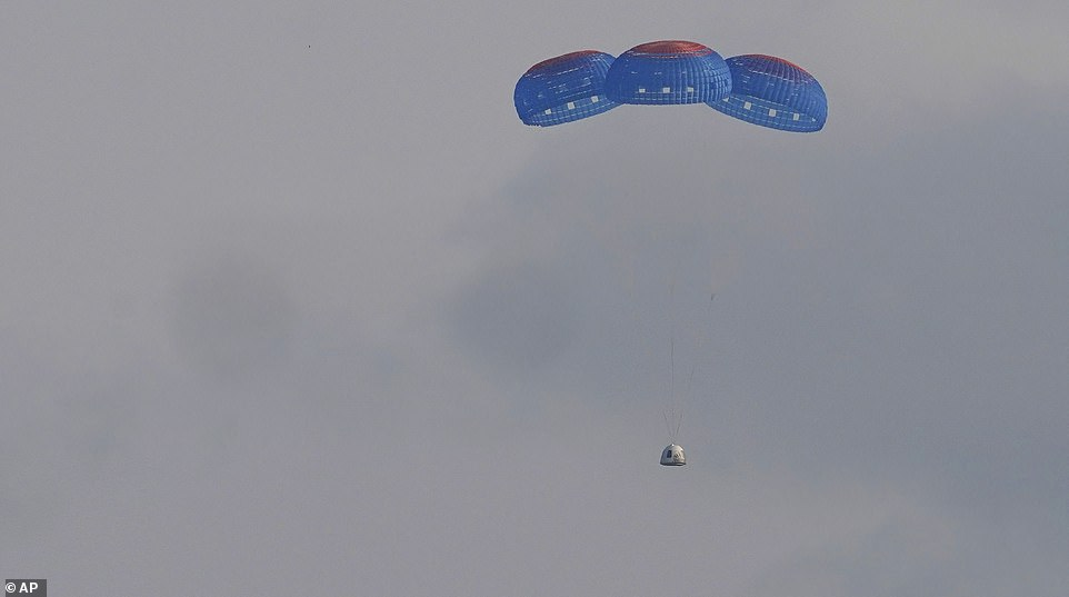 Jeff Bezos and the rest of crew Blue Origin return to earth in their capsule as it descends with three blue parachutes slowing its pace on Tuesday