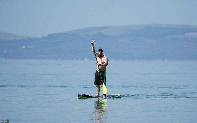 A man paddle boards in the sea off of Bournemouth beach in Dorset, as people enjoy this continued spell of hot weather