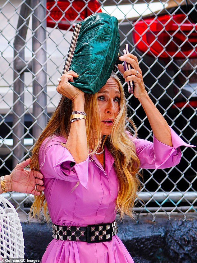 Emotional moment: Carrie even tried shielding her face with her cute green clutch