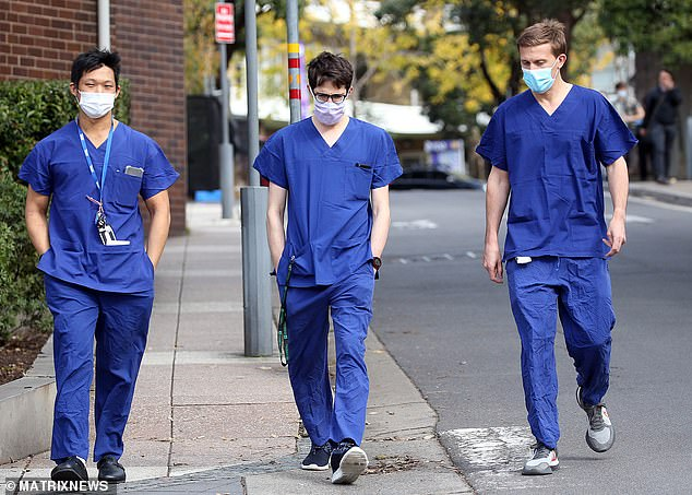 Lunch outside, please, boys: Medical staff at a Sydney hospital stroll the streets in their masks and regulation blues. Experts say the state has seen an invisible spread among essential workers in tea rooms and at shift handovers