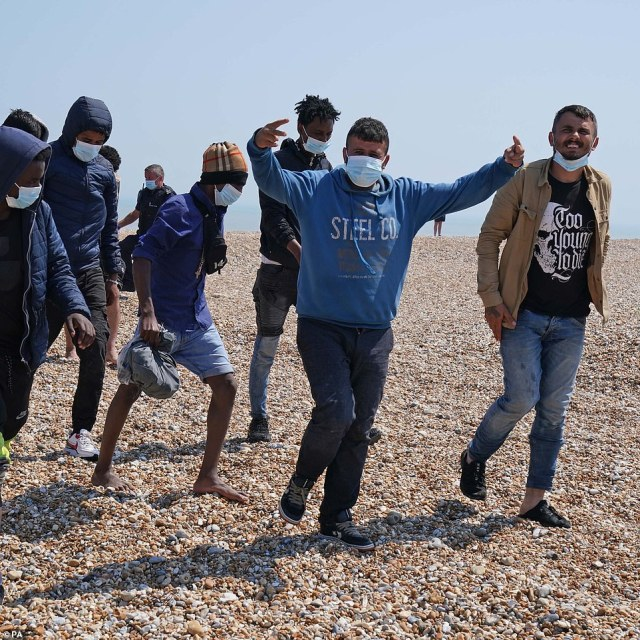 Pictured: A group of people thought to be migrants are escorted from the beach in Dungeness, Kent, by Border Force officers