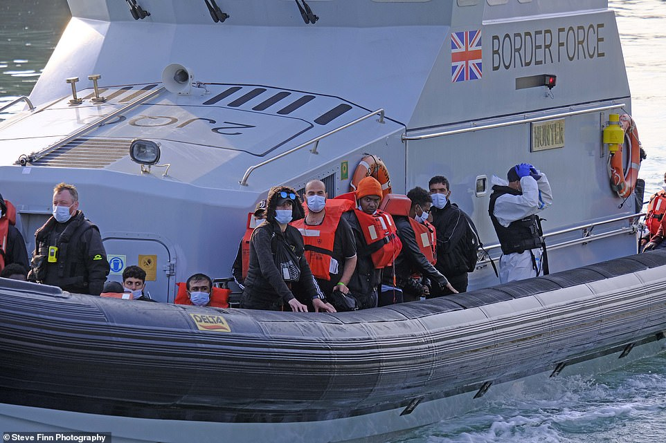A group of migrants wearing lifejackets and facemasks are taken ashore to Dover Marina in Kent this morning