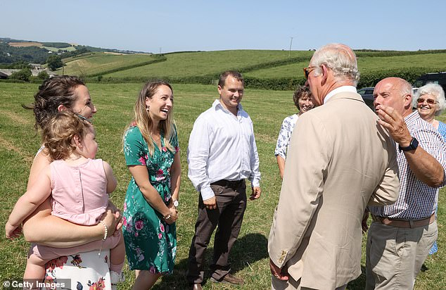 The Prince of Wales speaks with members of the Bellew family as he views Tennacott Farm and learns about their dairy ice cream business