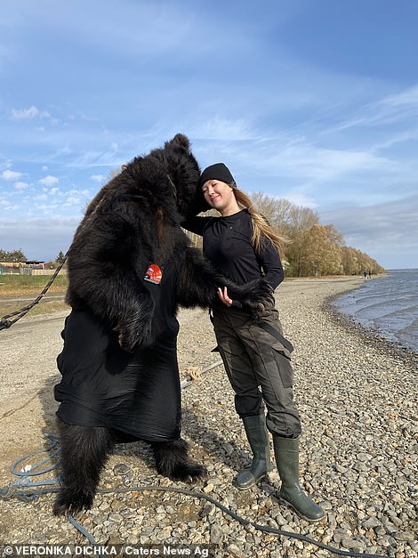 Archie and his ownerVeronika hug on the side of a lake in Russia