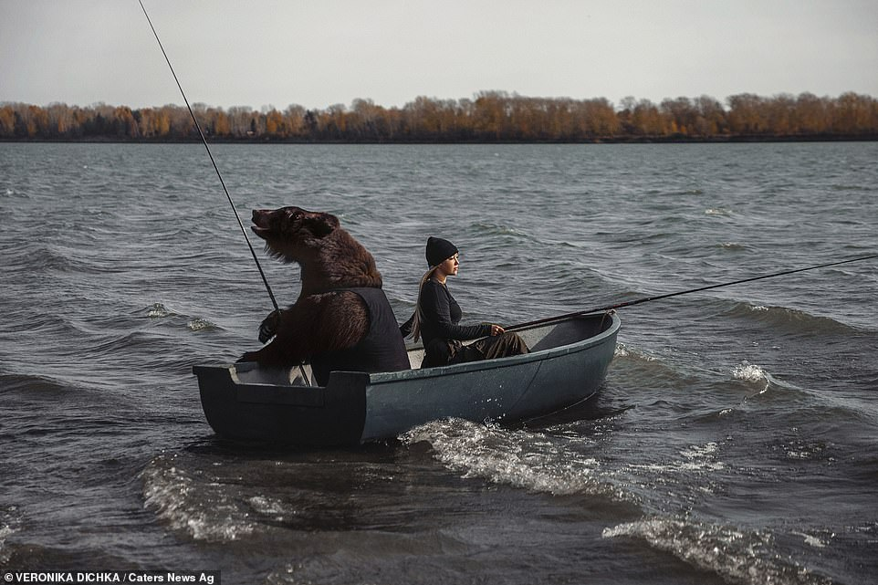 Veronika Dichka and her bear friend Archie sit in a rowing boat as they fish together on a lake in Siberia, Russia