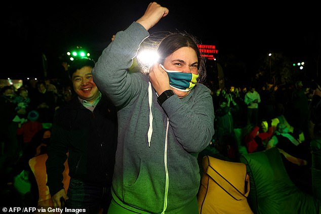 A Brisbane resident is seen celebrating after the announcement was made on Wednesday night