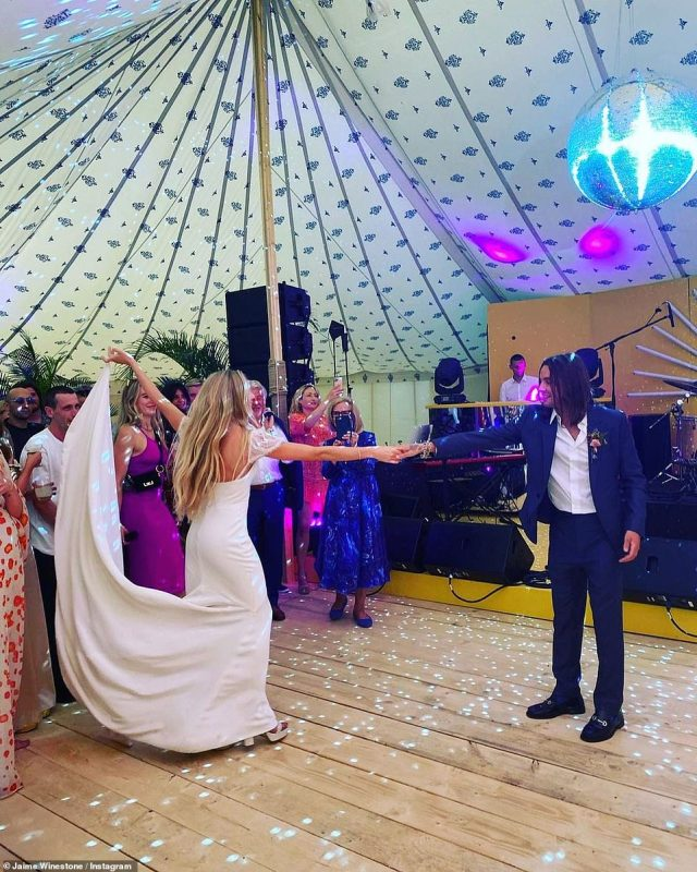 Taking to the floor: The couple showed off their dance moves underneath the tent canopy as their loved ones looked on. Clara kept her dress off the floor with a loop around her fingers